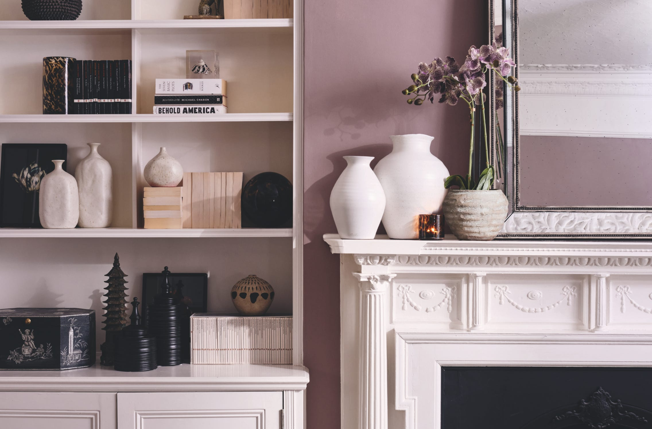 White shelving with monochrome accessories, next to a white mantlepiece