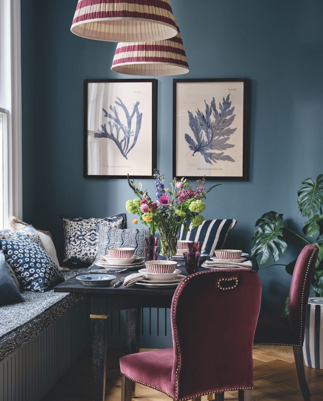 A colourful dining room with red velvet Stafford chairs, a table setting and a blue bench seat