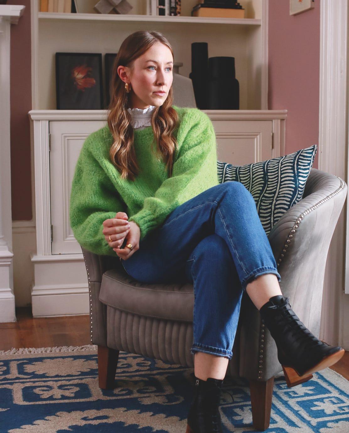 Erin Doherty wearing a green jumper, sitting in an Ash Grey Crosby armchair