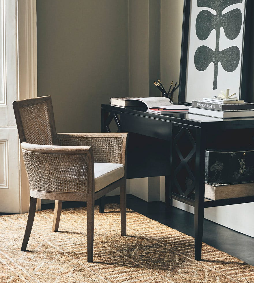 Rattan armed chair at a black desk