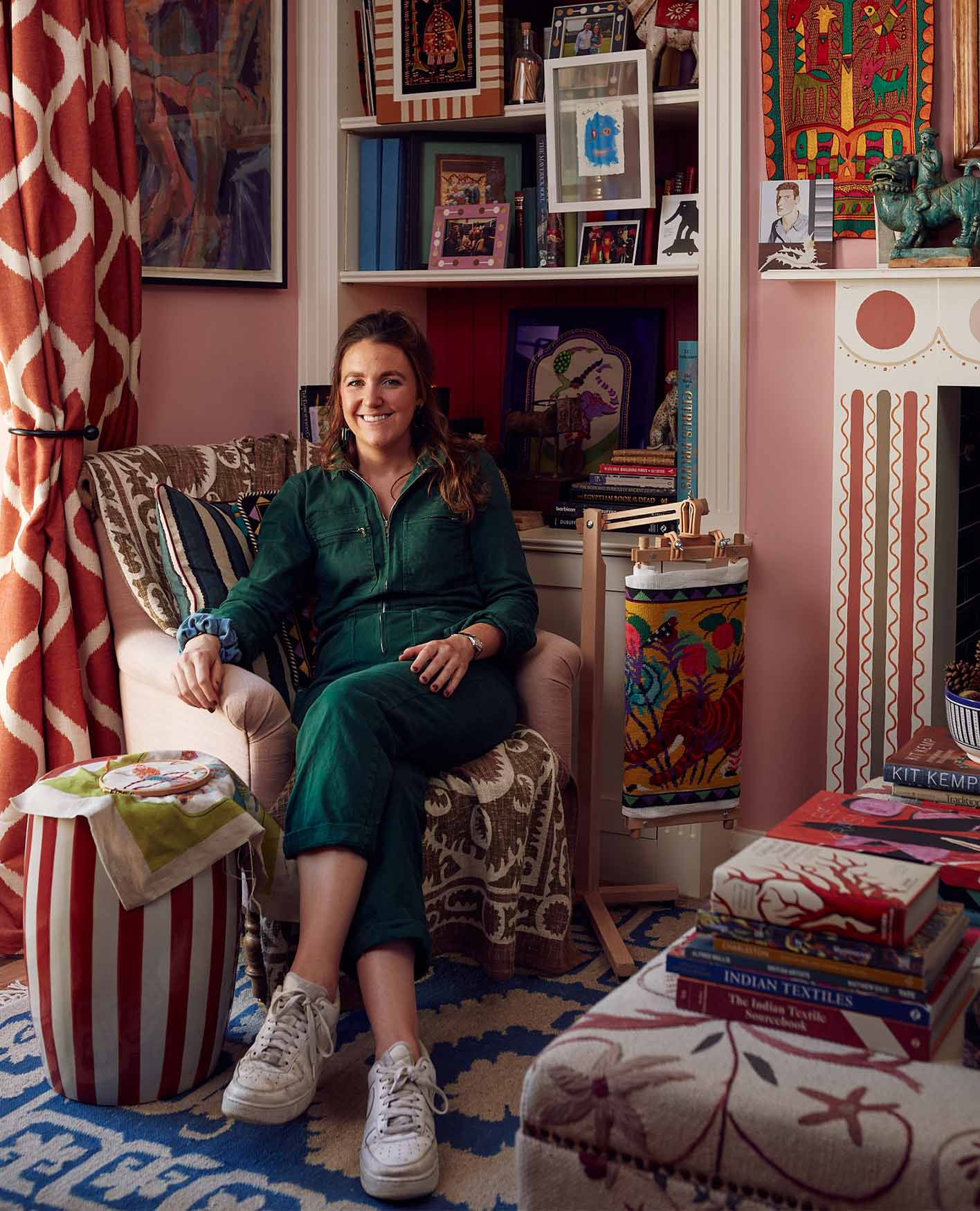 Eppie Thompson sat in her pink home in East London, wearing a green jumpsuit and surrounded by pattern and colour