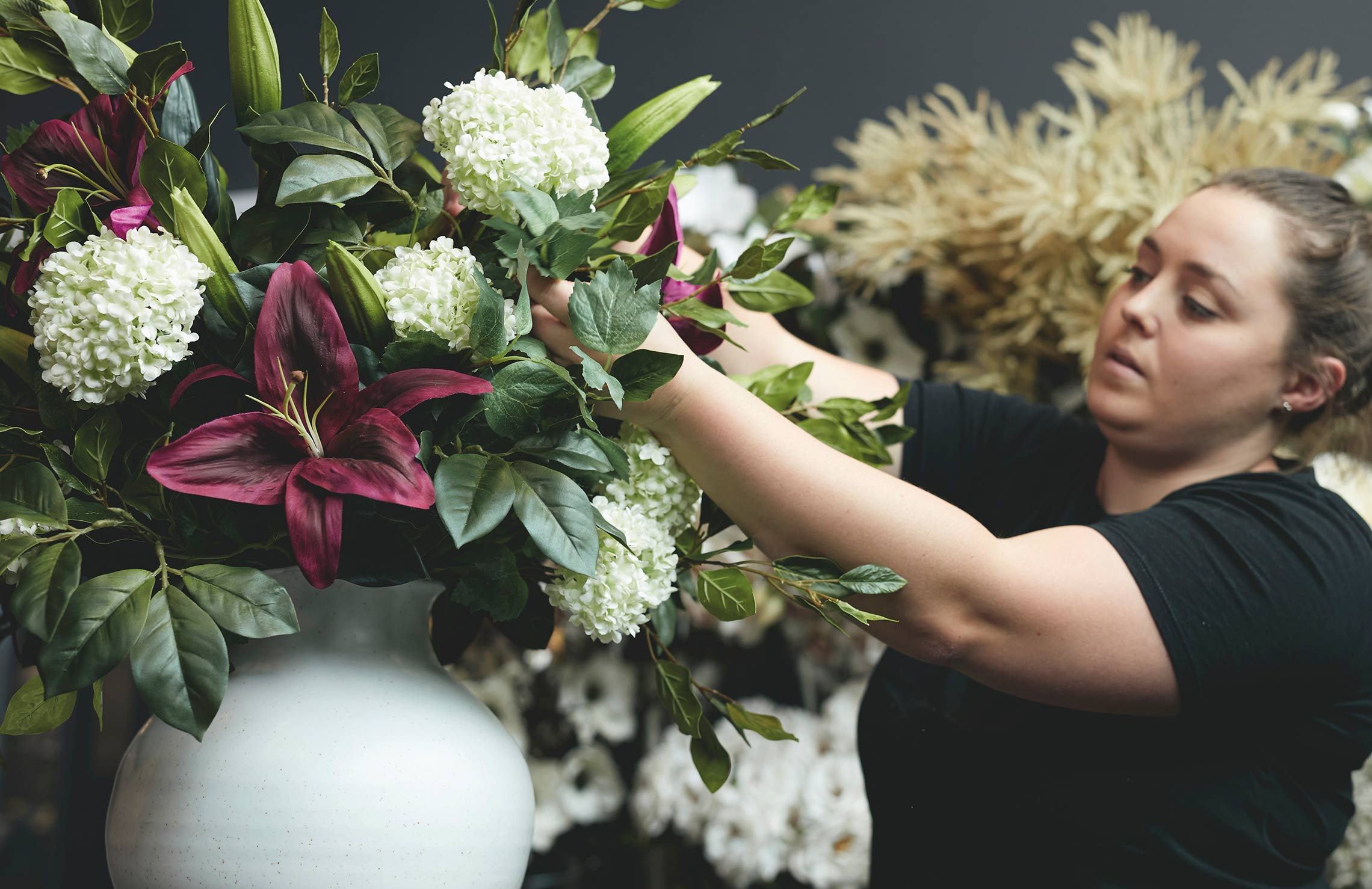 A woman exploring OKA's in-store faux flower arranging service