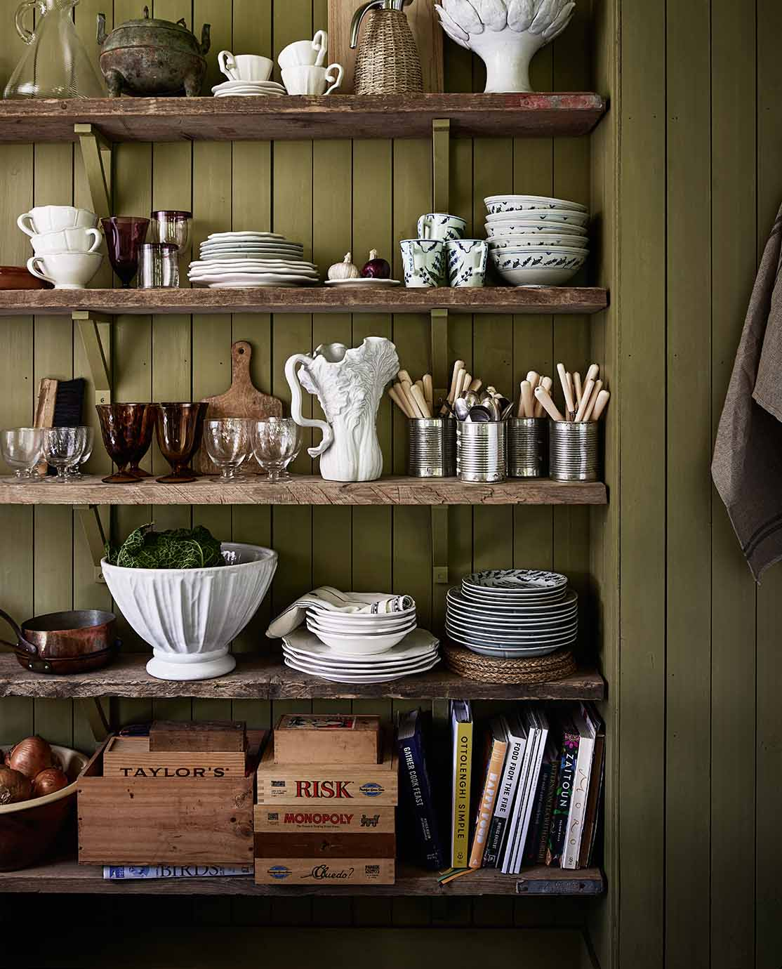 Green shelving with a mixed of white crockery and cutlery