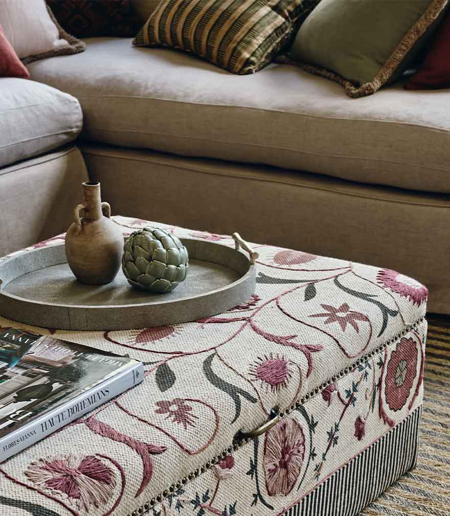 A faux shagreen tray with ornaments on top of an embroidered ottoman