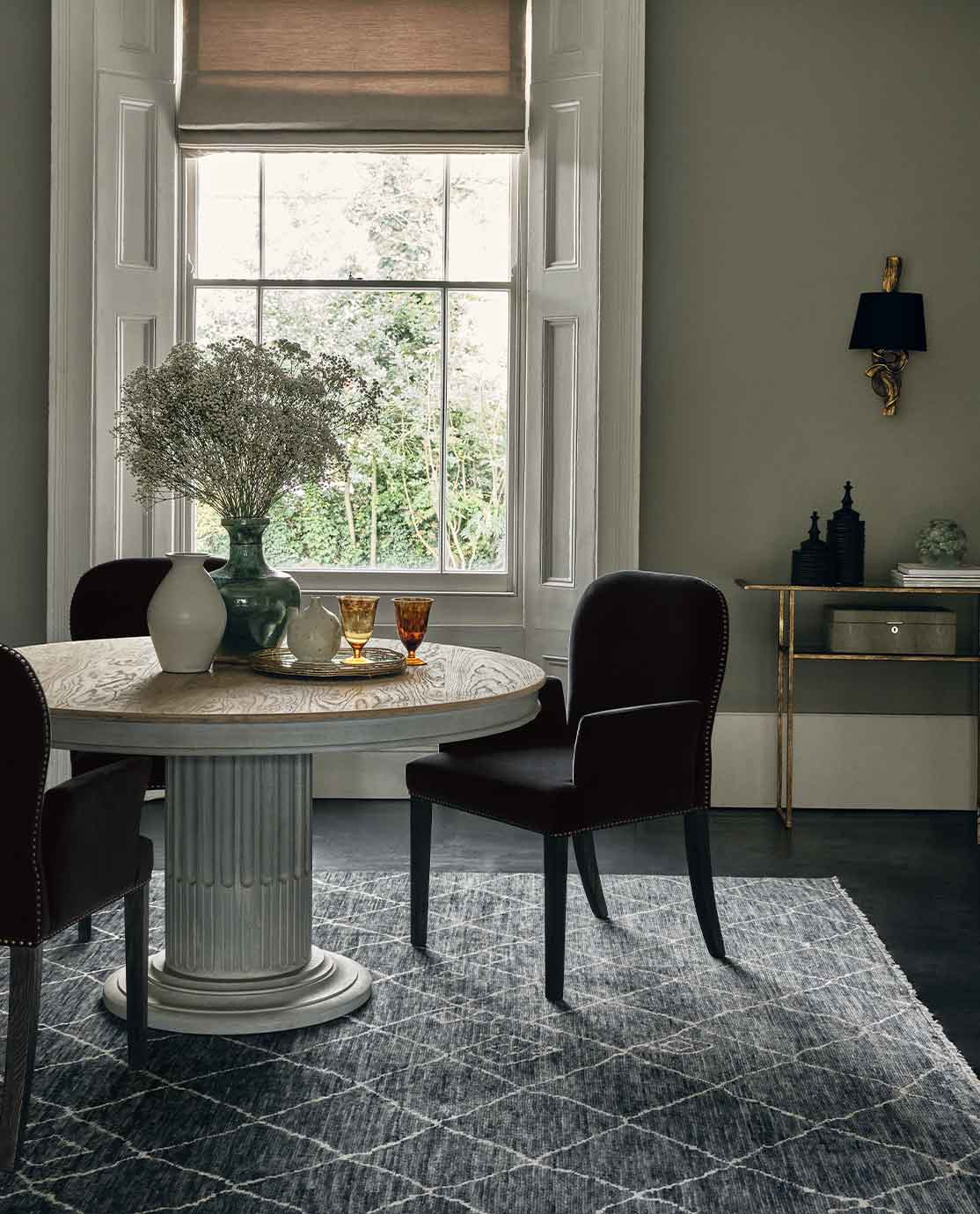 A rattan armchair in front of a black desk, decorated with a monochrome abstract print