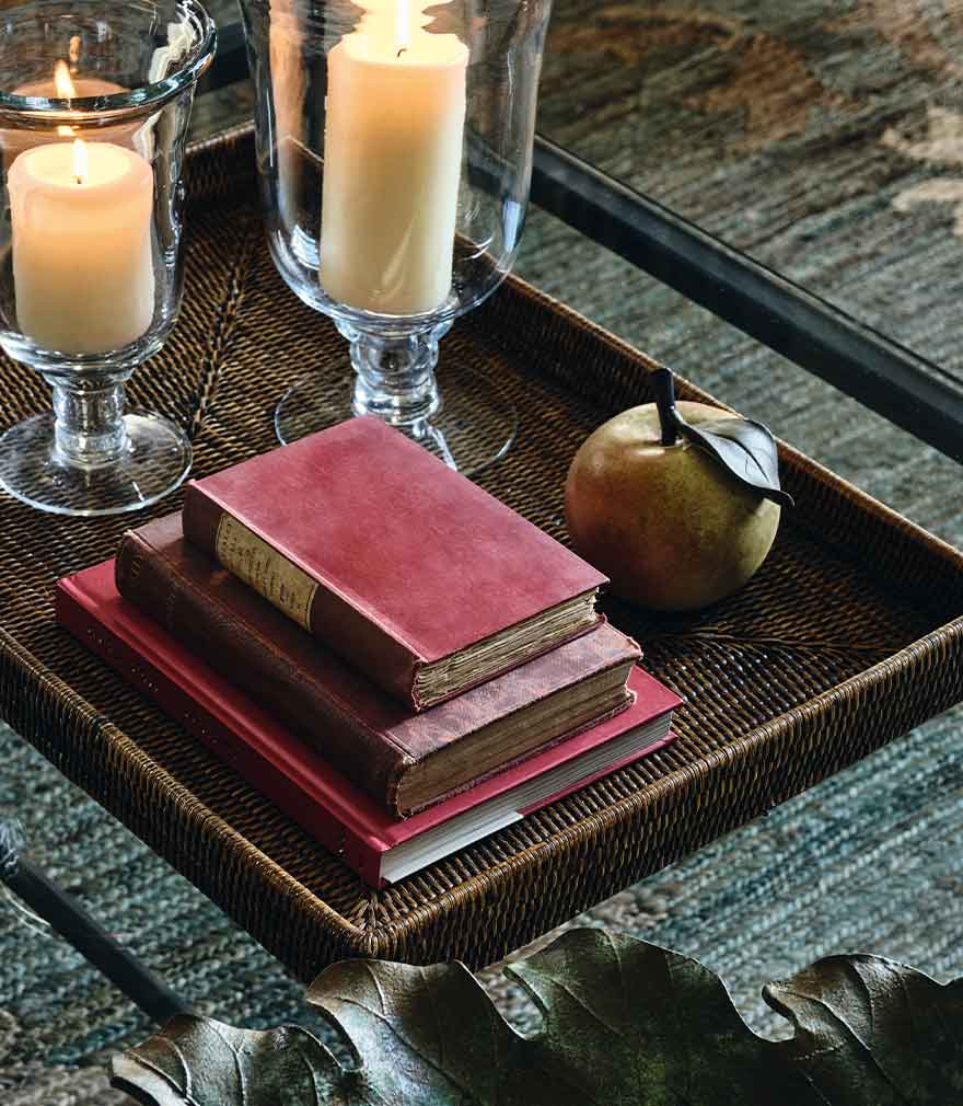 A stack of red books in a tray, next to a decorative apple and OKA's Glass Hurricane lamps