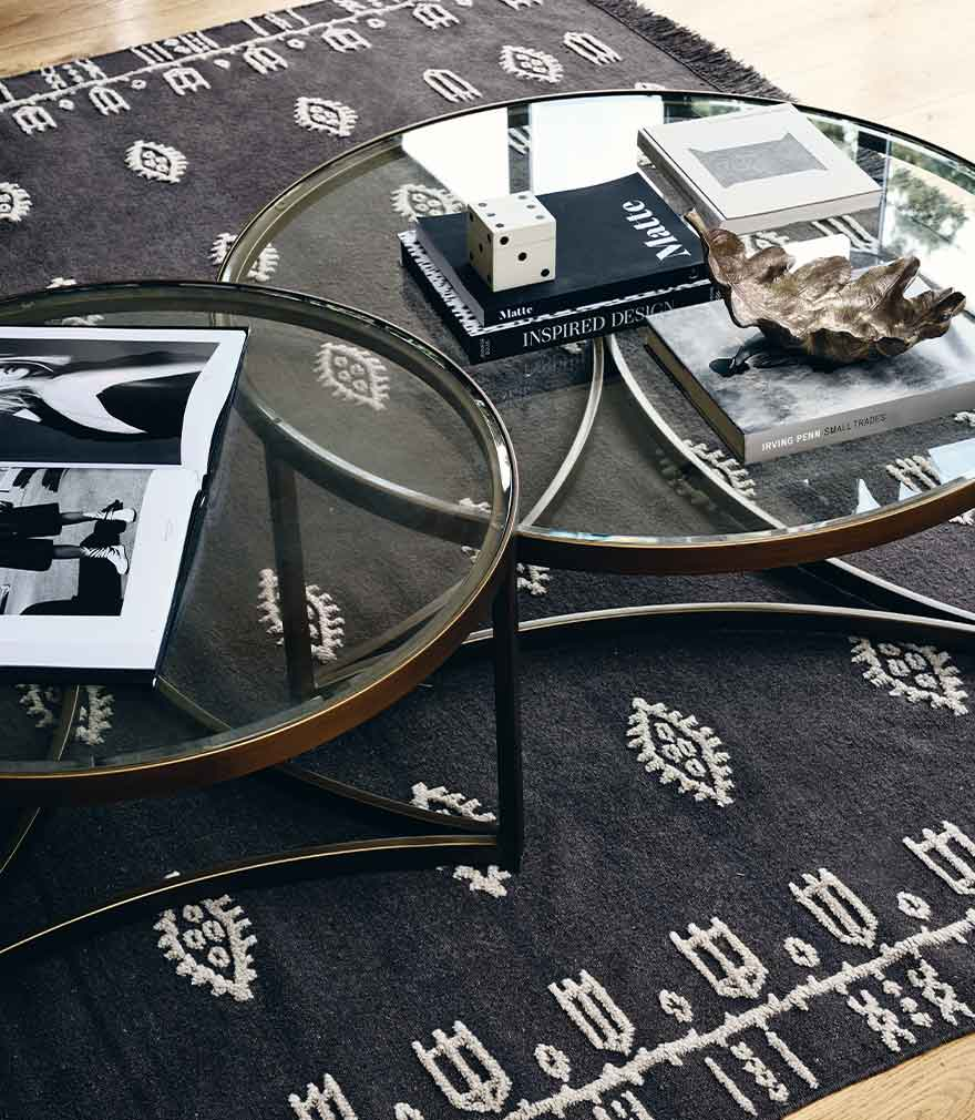 An arrangement of books and ornaments displayed on two glass circular coffee tables