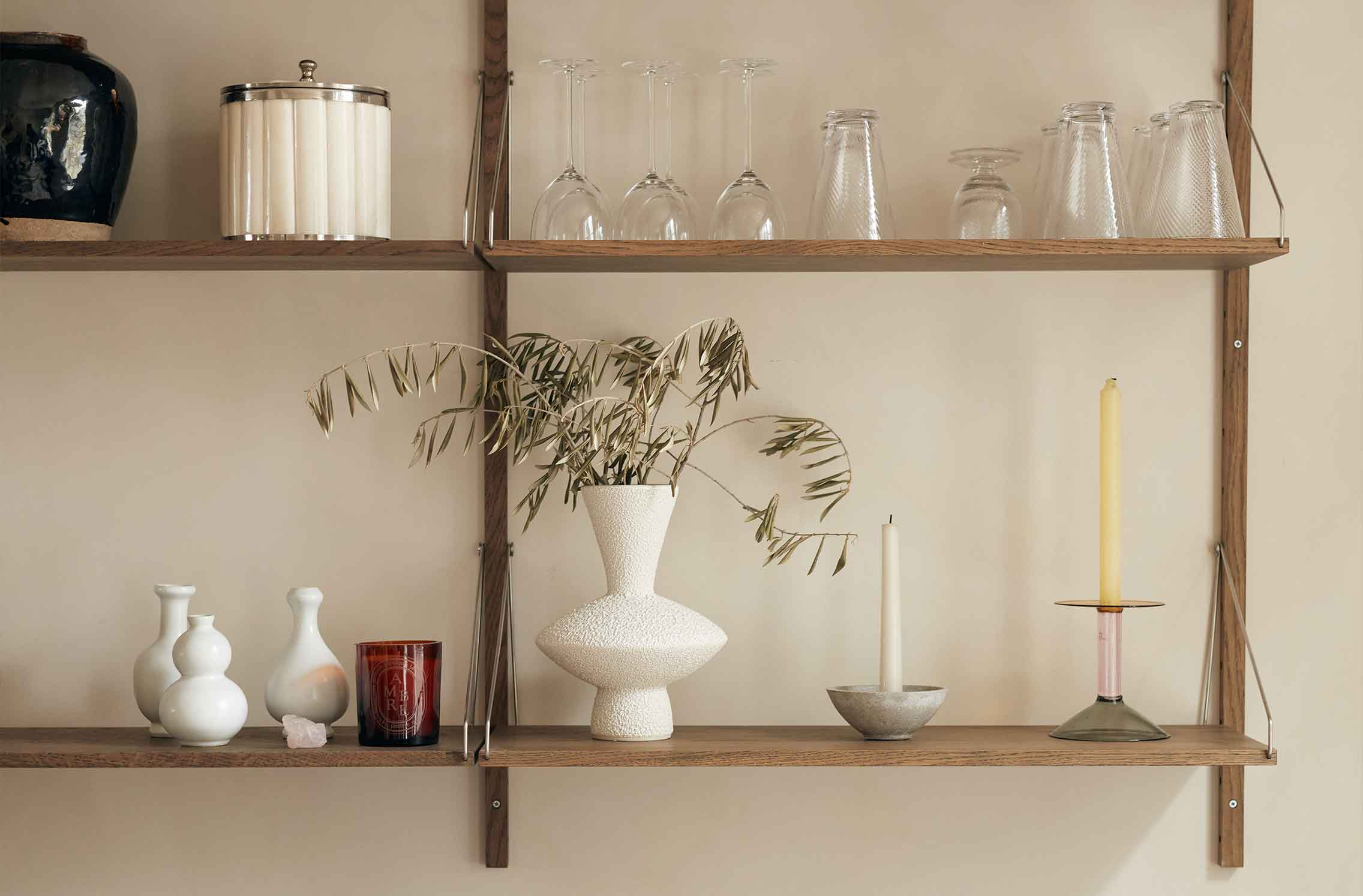 Ornaments and glassware arranged on wooden shelves