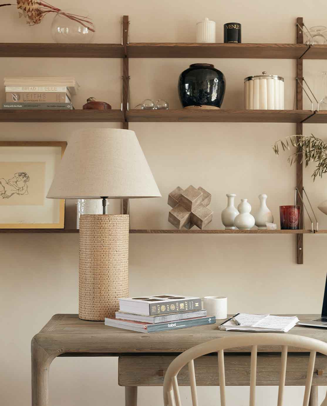 A desk and lamp in front of a shelving arrangement, all in neutral colours