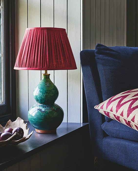 Green lamp sitting next to a navy blue armchair