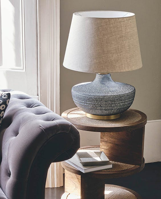 Velvet sofa flanked by a wooden side table with a lamp on it