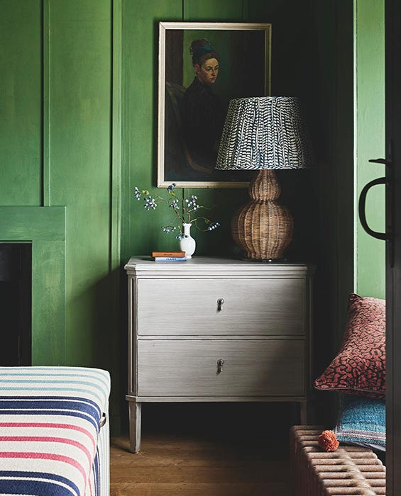 A green room with a small grey chest of drawers, topped with a rattan lamp