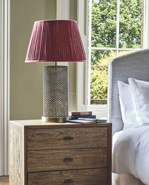 Next to a bed, there's a small wooden bedside table with a metal lamp on top