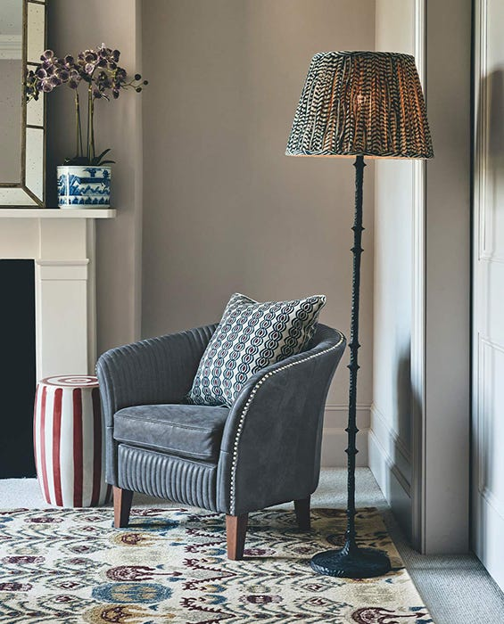A reading nook in the corner of a room, with an armchair and floor lamp