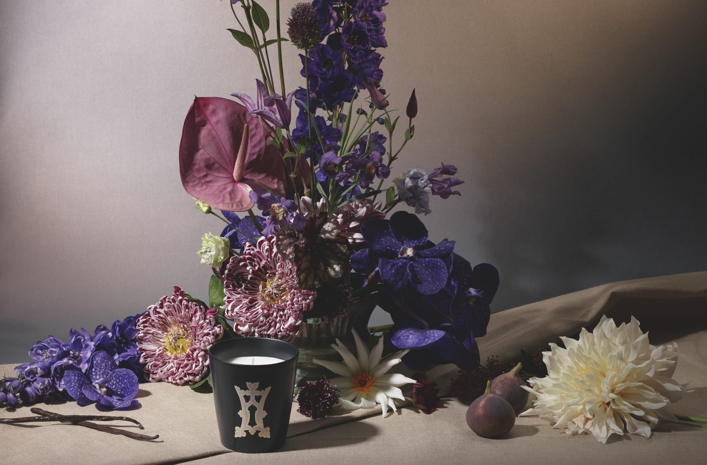 Clair de Lune candle in front of a bouquet of purple and pink flowers