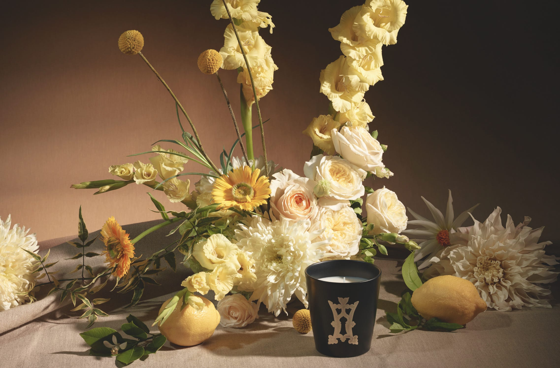 Herbes de Montagne candle in front of a bouquet of yellow and white flowers