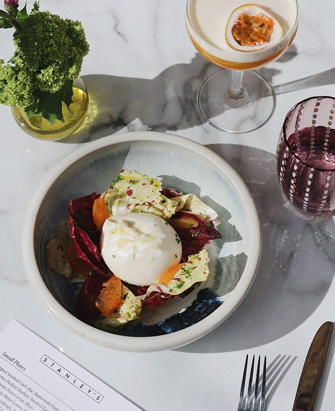 Bowl of salad and burrata on a marble table