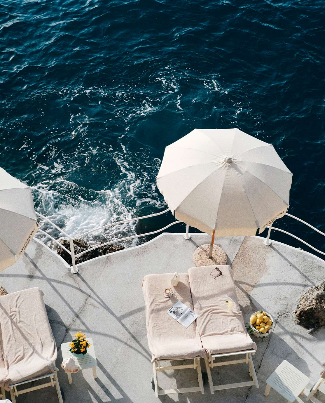 Aerial view of two white sunloungers overlooking the Amalfi Coast