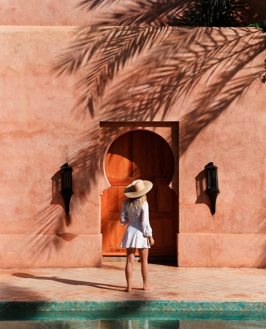 Woman wearing a straw hat and white dress in front of a Moroccan building