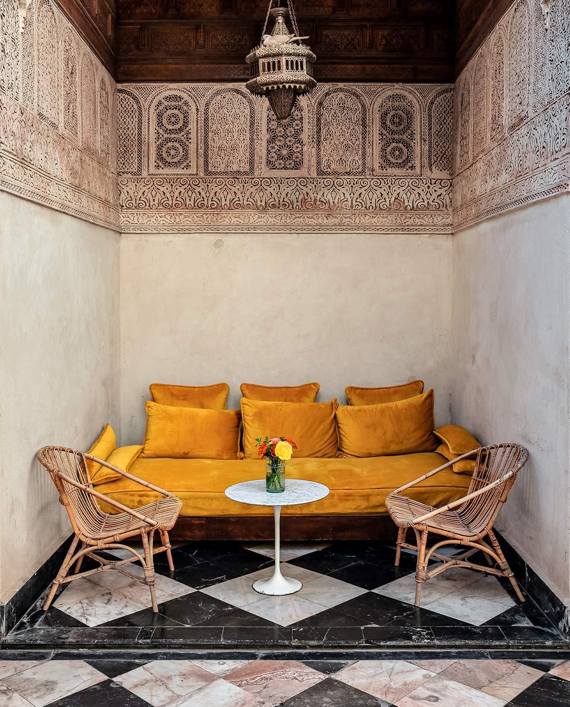 Velvet, mustard yellow sofa in a black-and-white tiled room