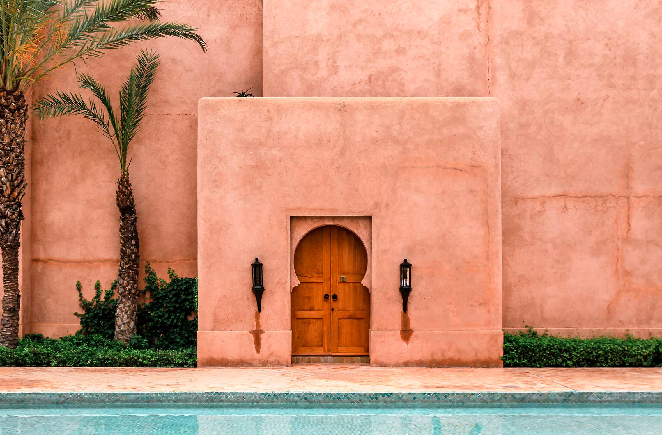 Red-walled building in Morocco overlooking a swimming pool