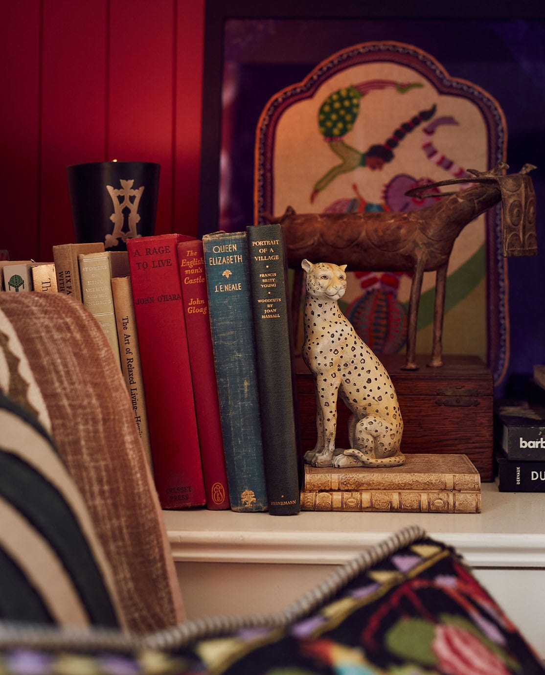 OKA's leopard Lakadema bookend supporting a selection of antique books