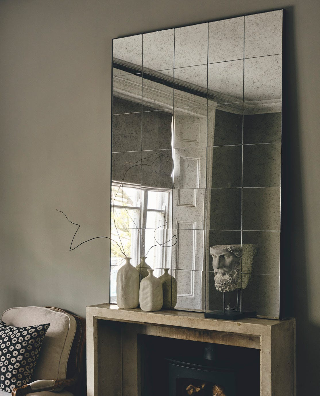 A large rectangular distressed-effect mirror takes centre stage on a console table