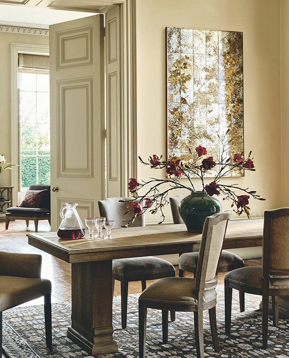 A grand country house dining room with a huge table, chairs and mirrored wall art