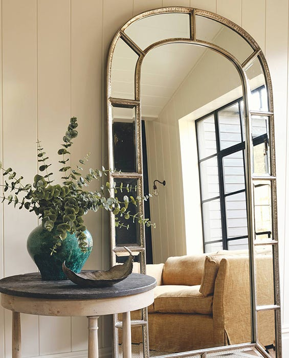 A huge arched window mirror reflects a contemporary sitting room