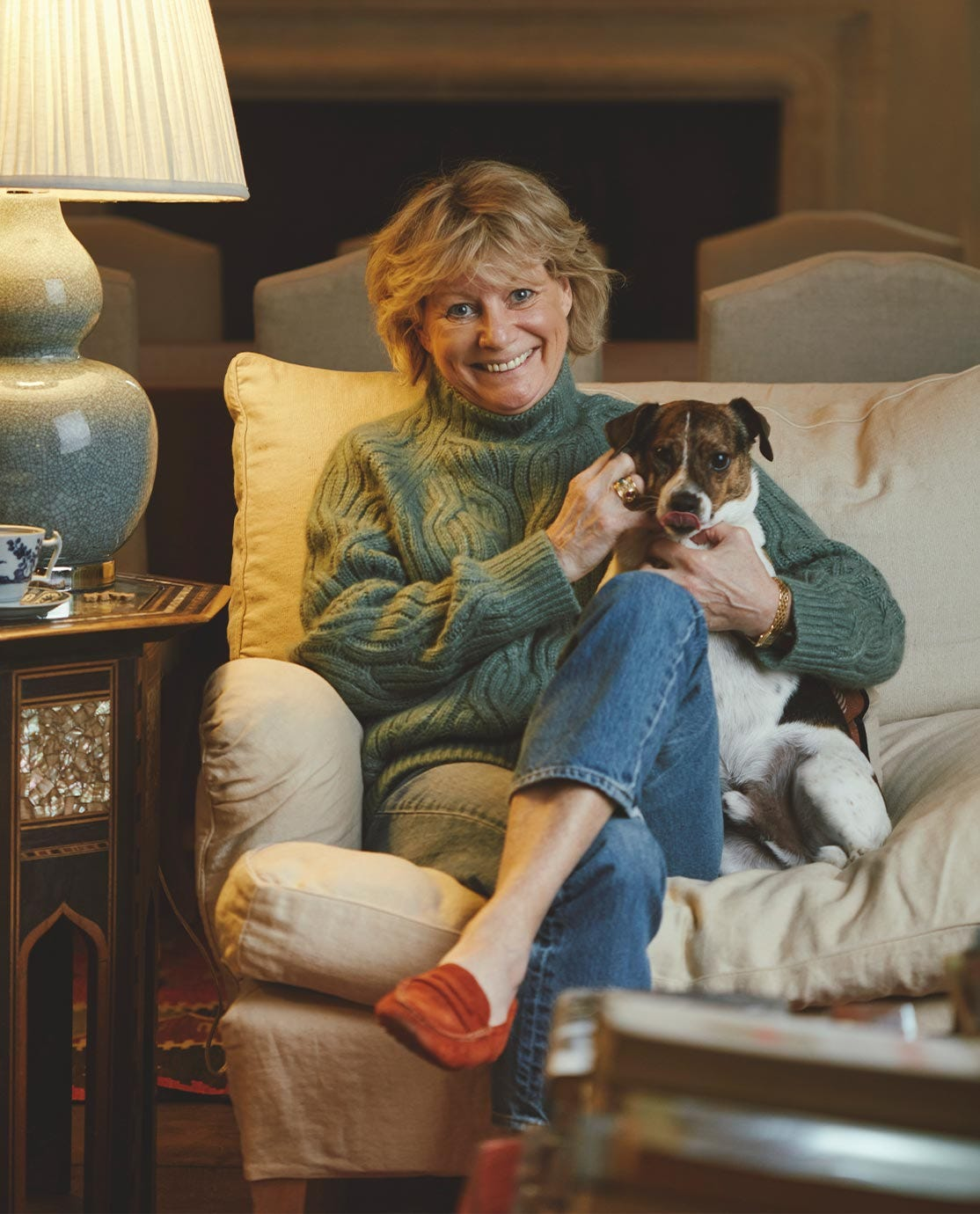 Sue Jones and her Jack Russell sat on a white sofa