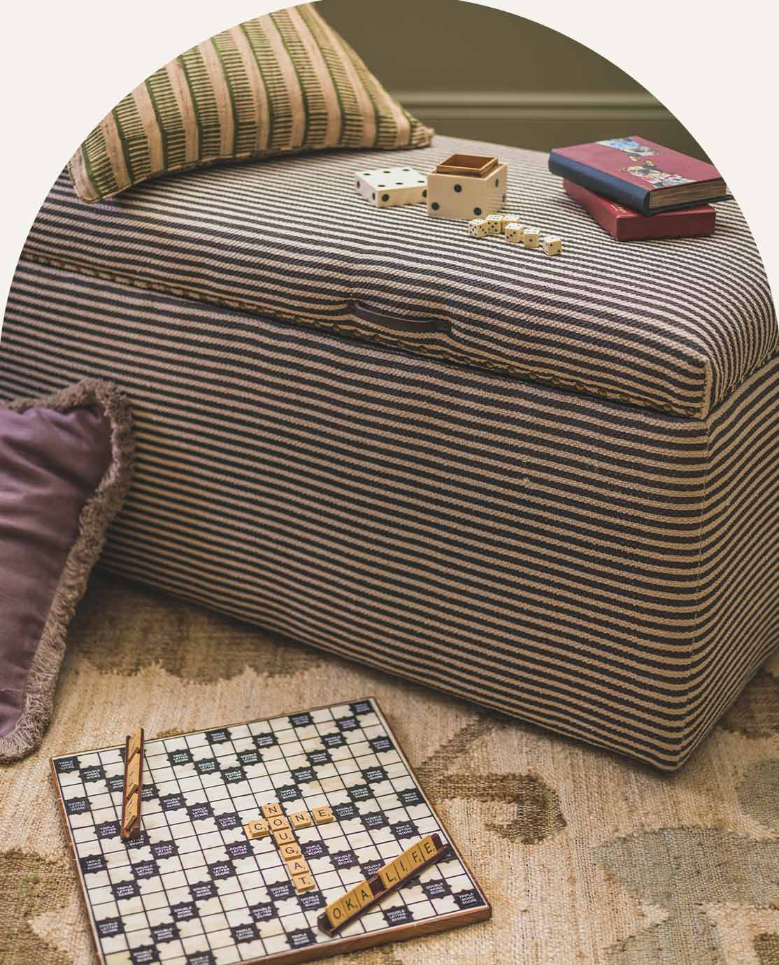 Striped ottoman, board games and cushions