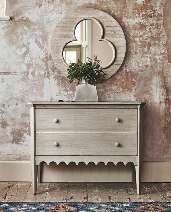 A clover-design mirror on a wall draws the eye above a petite chest of drawers