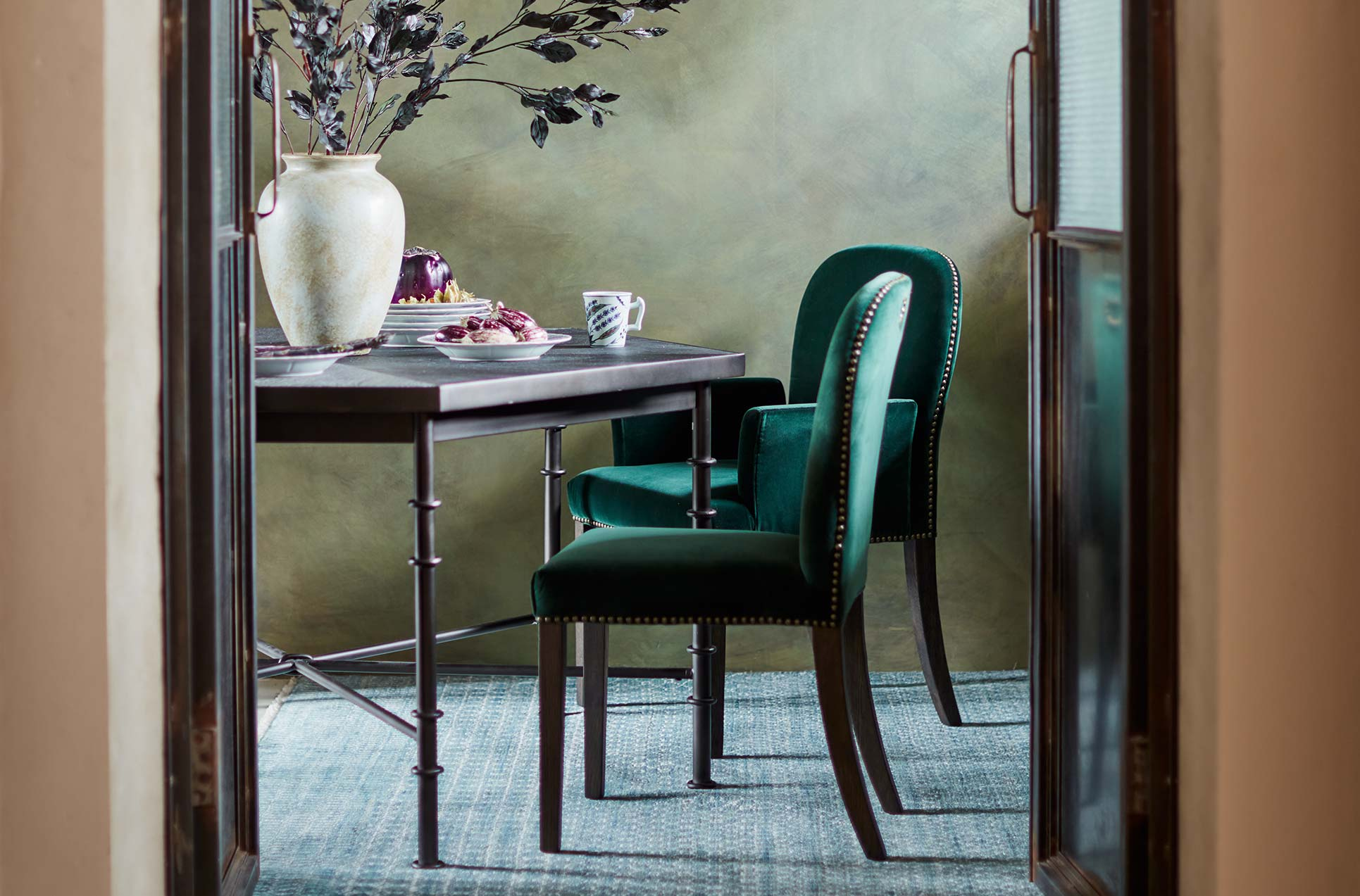Green velvet Stafford chairs around a black dining table