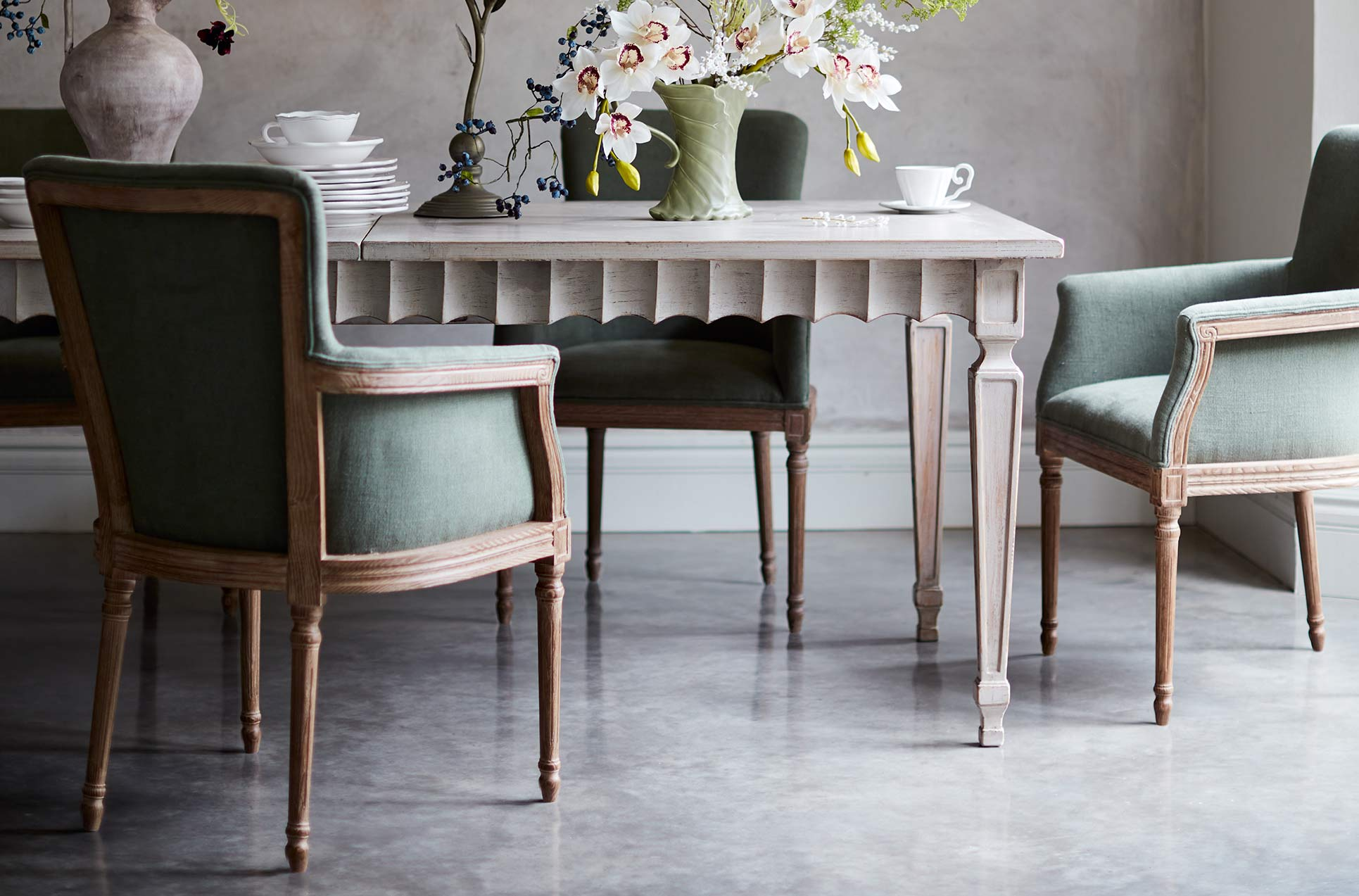 Green linen dining chairs with arms around a light wood dining table