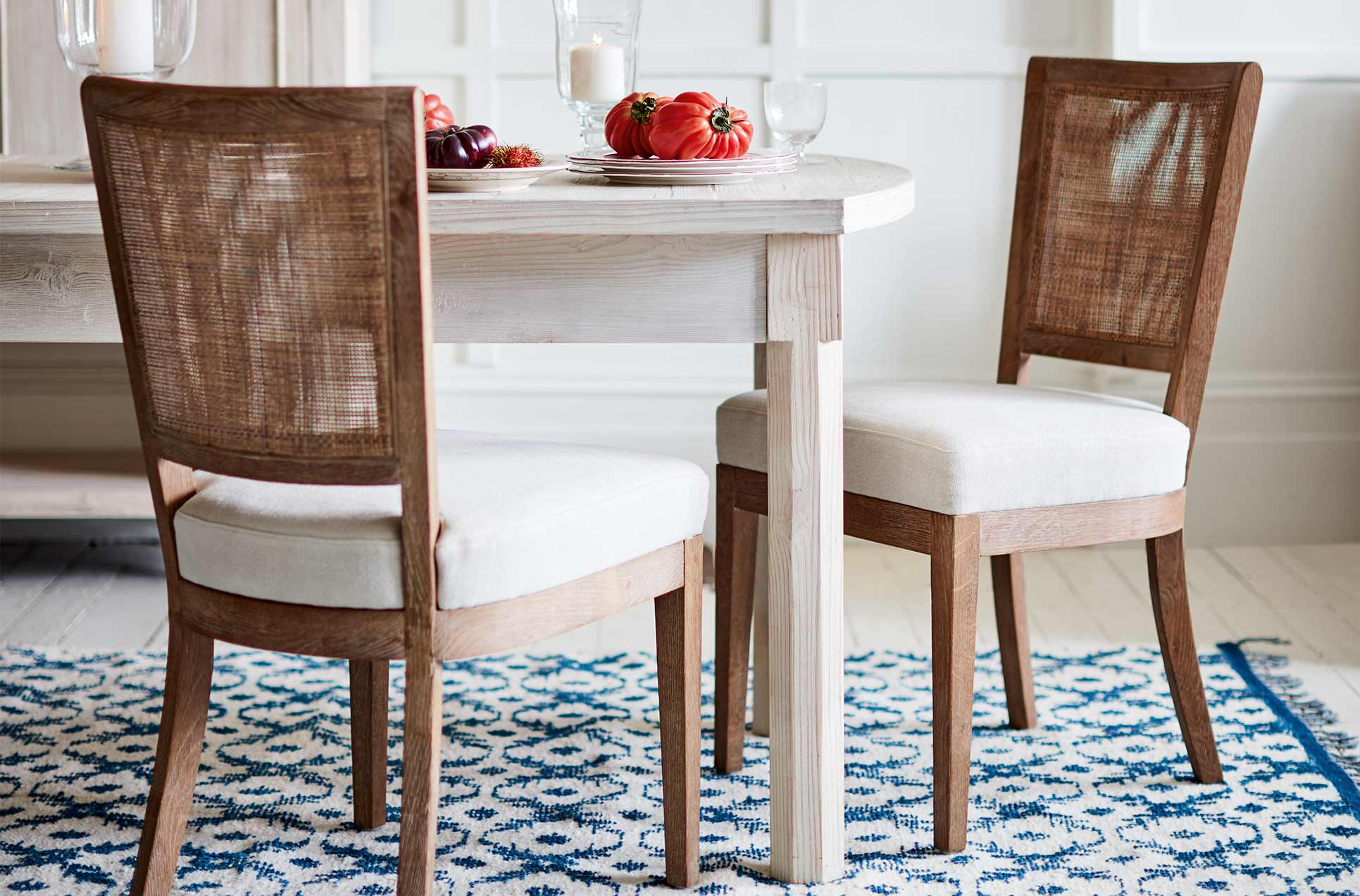 Rattan dining chairs with a linen seat around a light wooden table