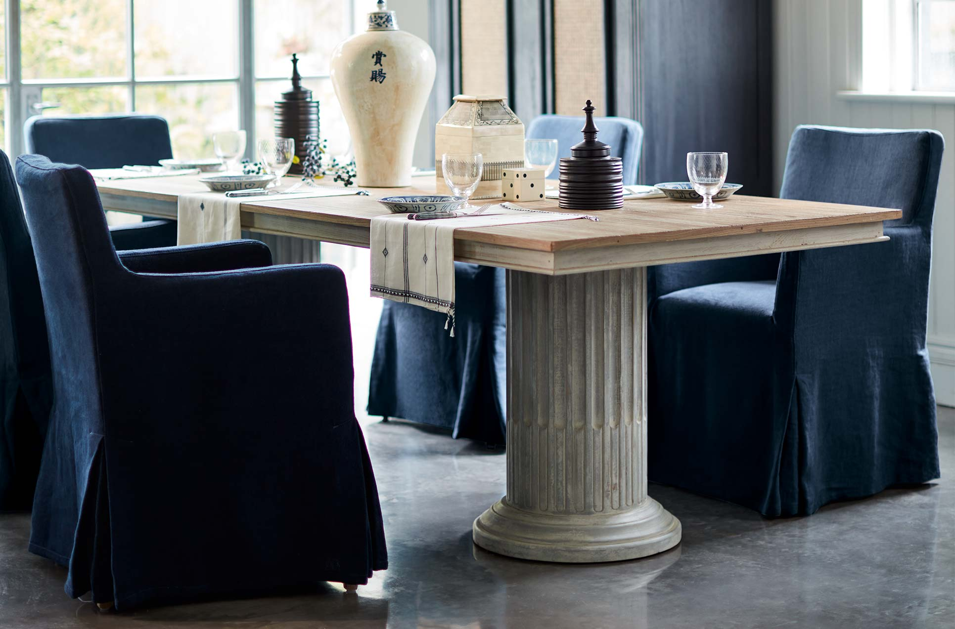Navy linen loose covered dining chairs around a wooden table with column-style legs