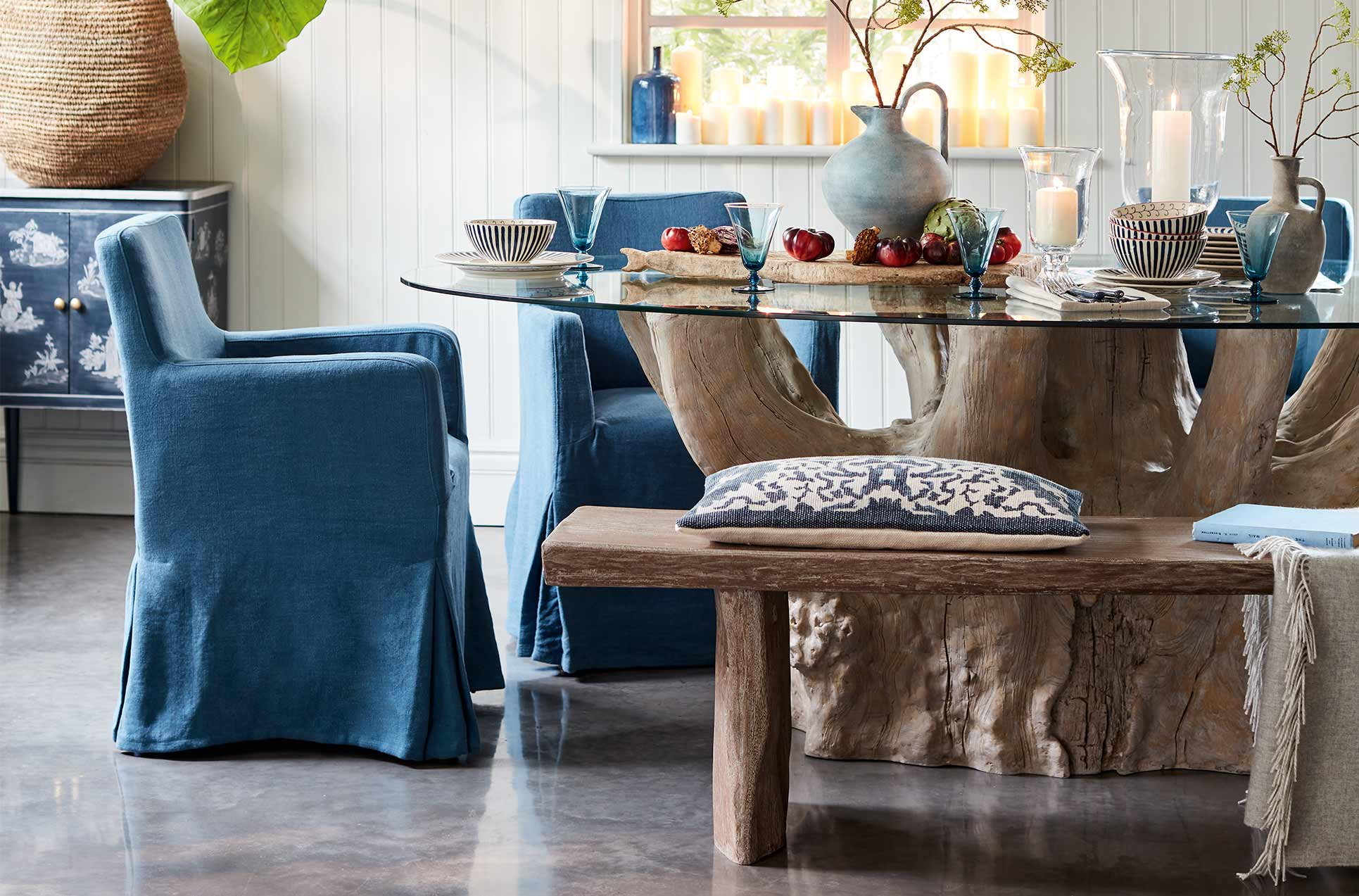 Navy linen loose covered dining chairs and a wooden bench around a glass-topped dining table with a tree trunk-style base