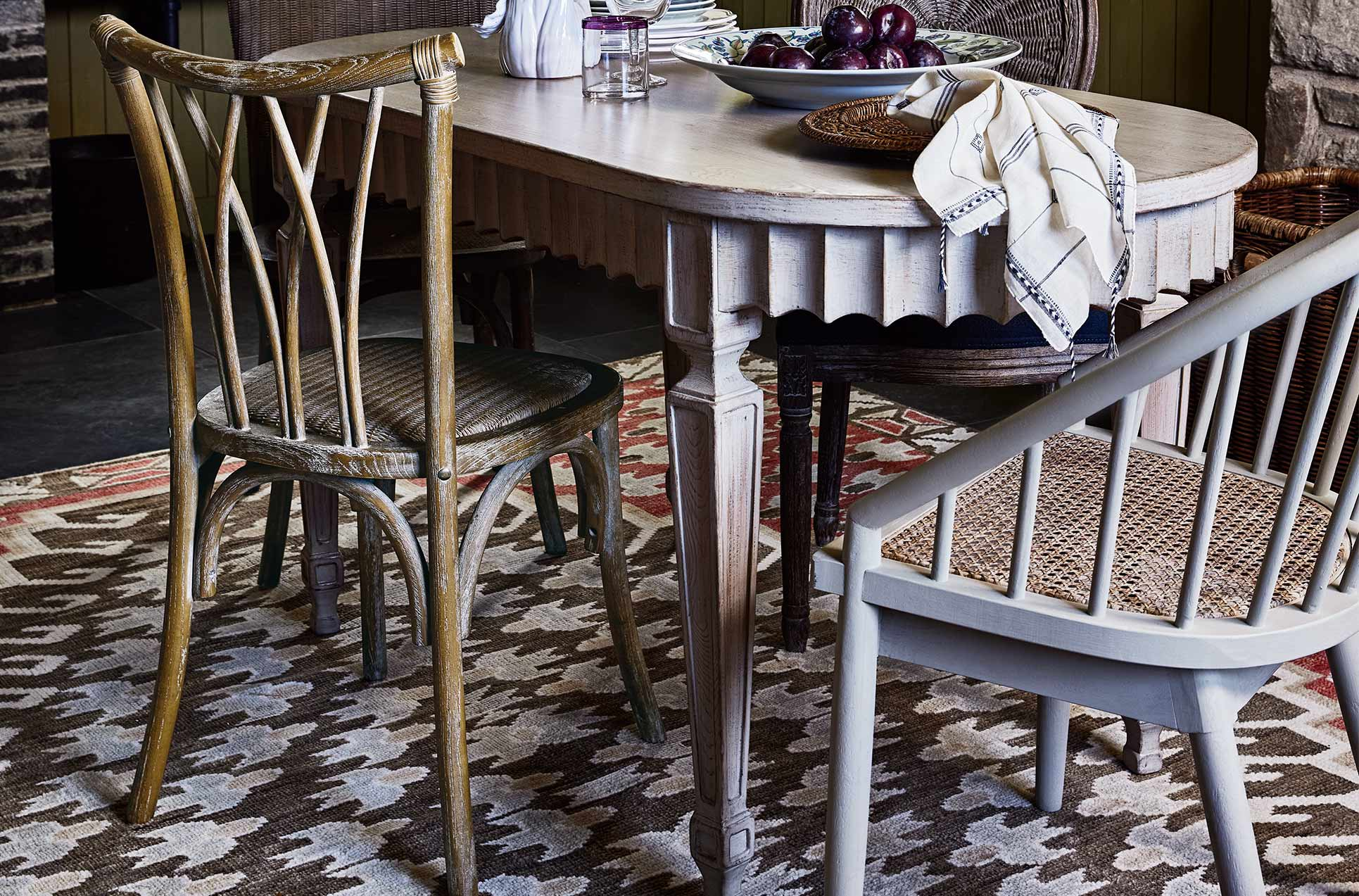 Rattan dining chairs around a light wooden table with pleated detailing on the edge