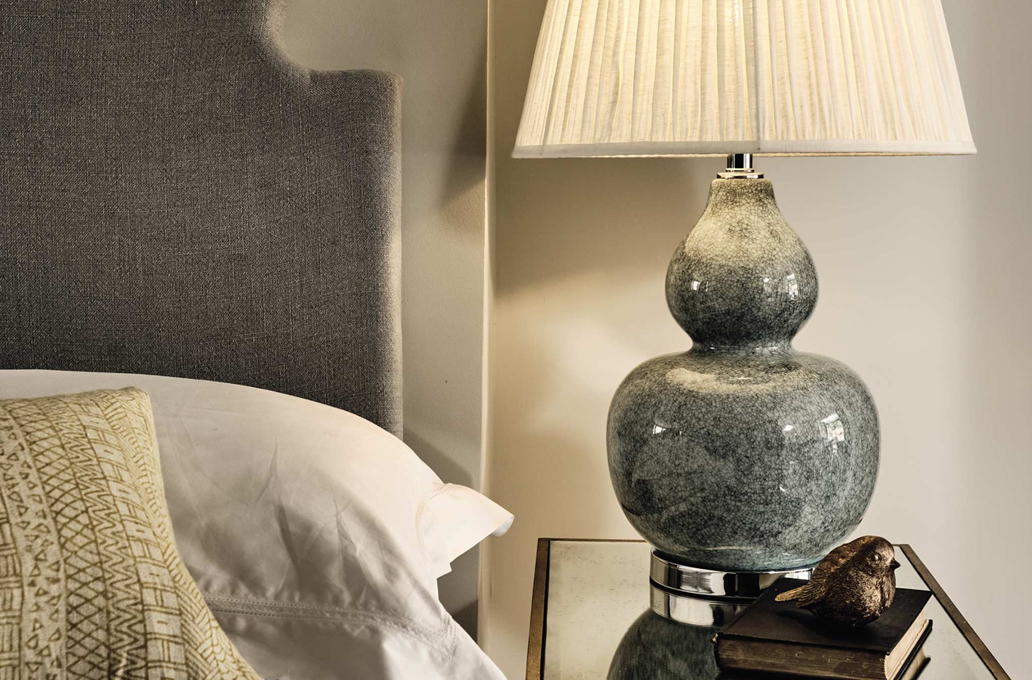 A ceramic gray table lamp with a white pleated shade, on top of a glass sidetable