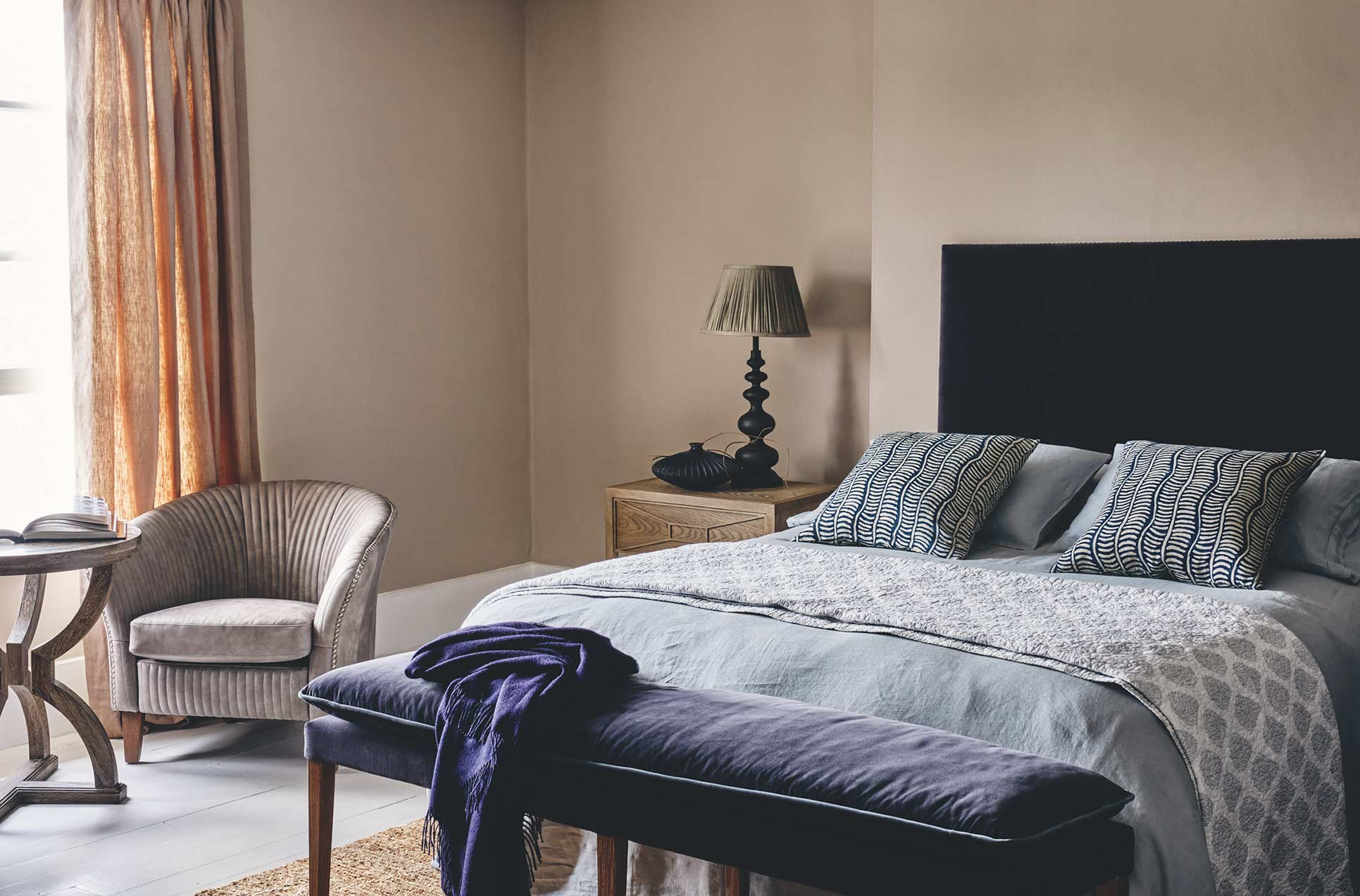 A blue-themed bedroom, with a blue velvet bed, black table lamp and navy velvet bench seat