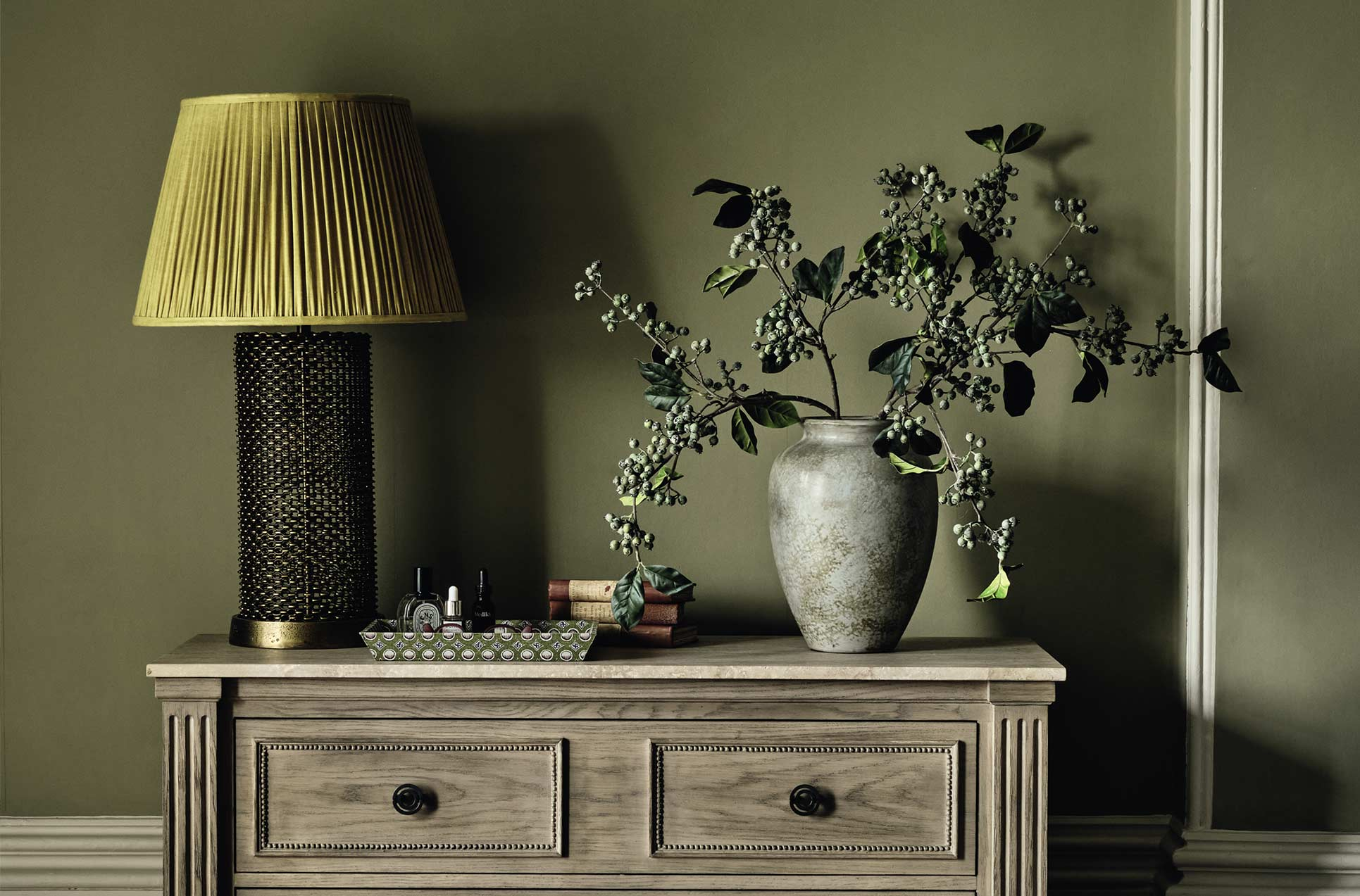 Glass table lamp with a yellow pleated shade, on top of a wooden chest of drawers
